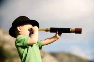Young boy looking through a telescope